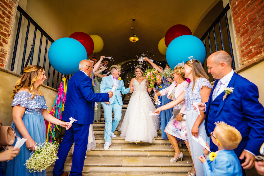 Kerry & Leah walk down steps of Farnham castle as their friends and family throw confetti with colourful balloons either side
