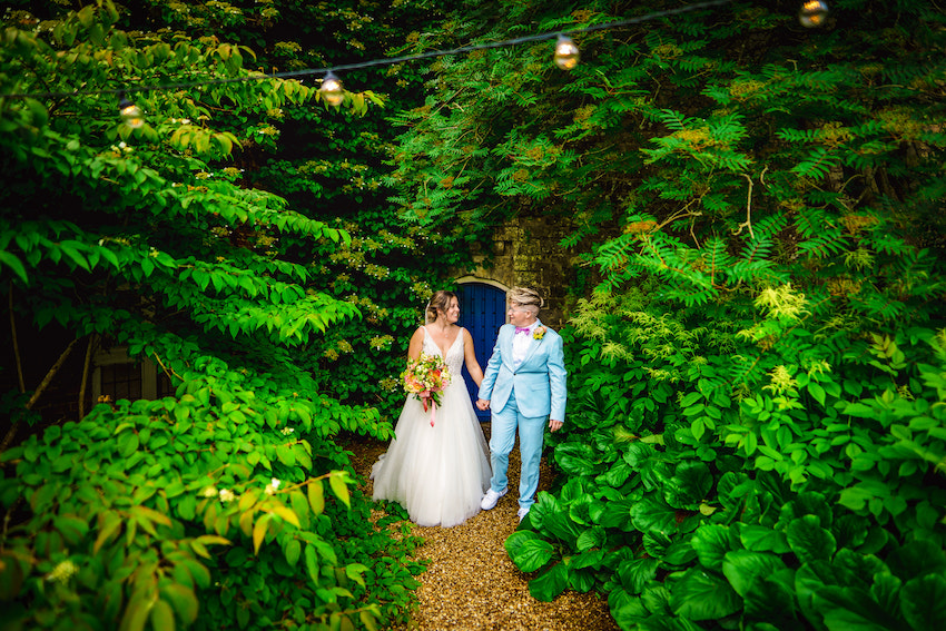 Kerry and Leah had hands and look at each other surrounded by greenery