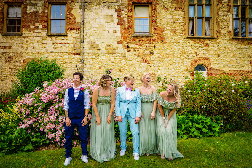 Kerry stands with bridal party outside Farnham Castle