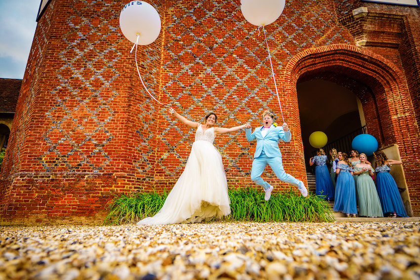 A mix of classic and colourful as Kerry & Leah jump for joy holding giant white balloons outside Farnham Castle