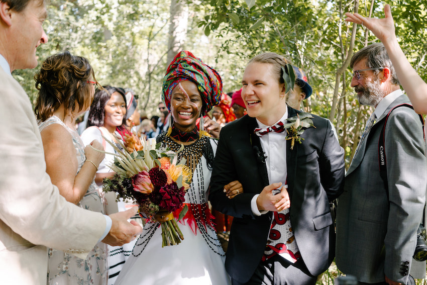 South African wedding - bride and groom smiling walk arm in arm with guests on either side