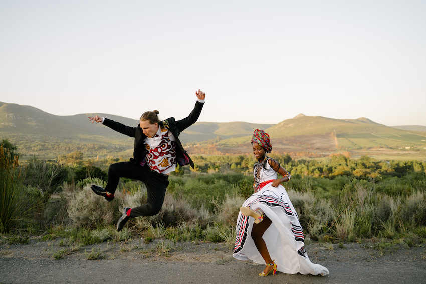 African bride in traditional wedding attire dances and her groom jumps in air with South African landscape behind them