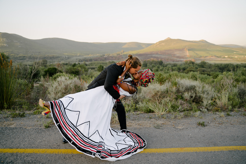 Bride leans back in Grooms arms as he kisses he kisses her, with South African landscape behind