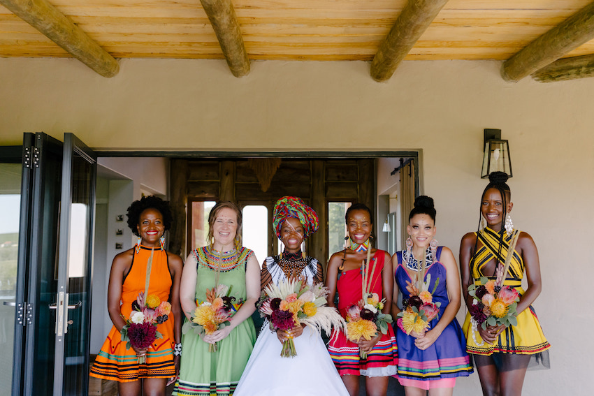 South African bride Nozzi stands with her bridesmaids in colourful dresses all holding bouquets of flowers