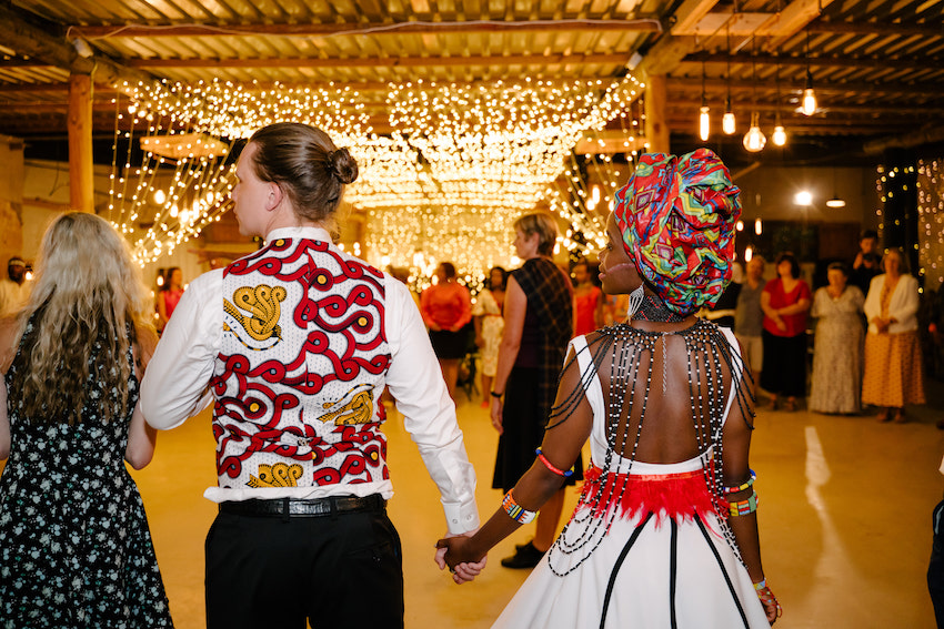 bride and groom holding hands at wedding reception. Groom wears bright waistcoat and bride traditional African clothing