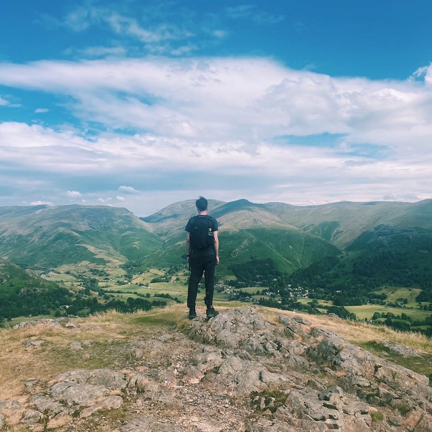 Man standing on top of mountain looking down over Lake District views