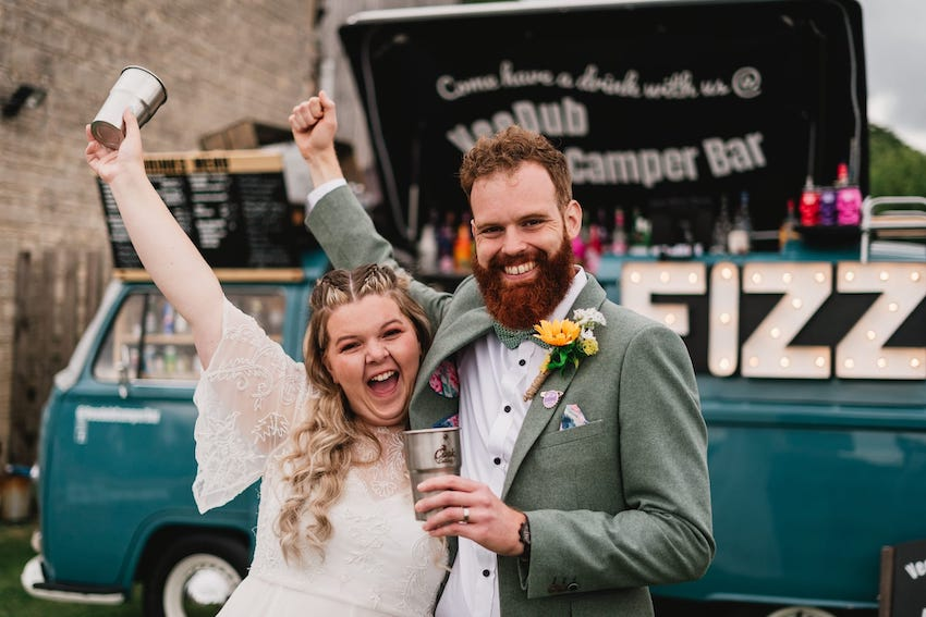 Bride (white woman wearing lace dress) and Groom (white man wearing sage coloured suit) fist pump the air, with big smiles on their faces, behind them is a 'campervan bar'