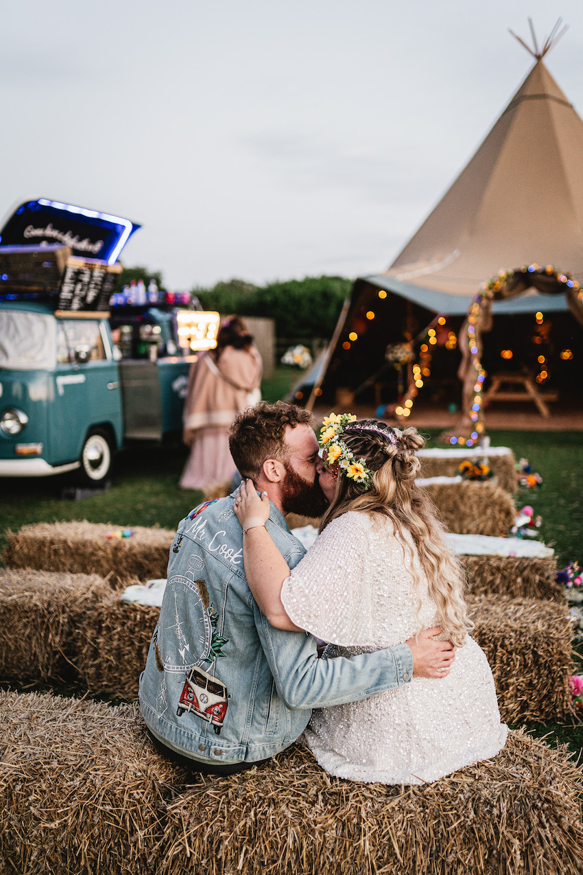 Bride (white woman in lace dress and flower hair garland) and Groom (white man with short hair and beard wearing denim jacket) embrace and kiss sitting on a hay bale on their wedding day, with tipi and campervan behind