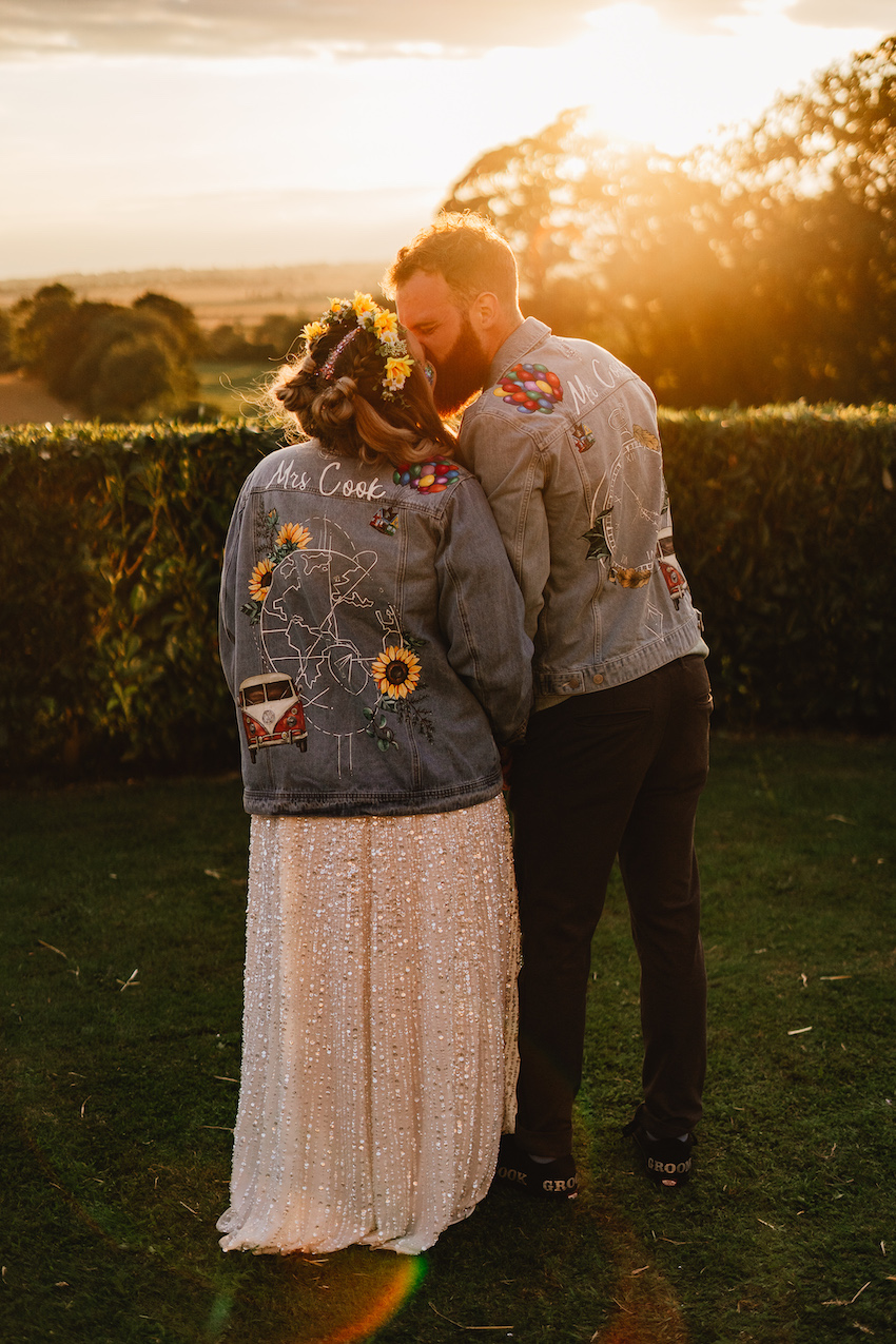 Bride (white woman in lace dress and flower hair garland) and Groom (white man with short hair and beard both wearing denim jacket) hold hands and kiss with greenery and golden sunset behind them