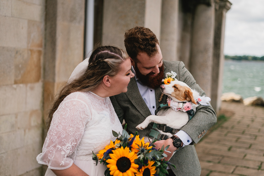 Bride Lucy wearing a lace dress and holding sunflowers, and Groom Richard wearing a sage green suit, stand together on their wedding day cradling their dog Bella who wears a flower neck garland.