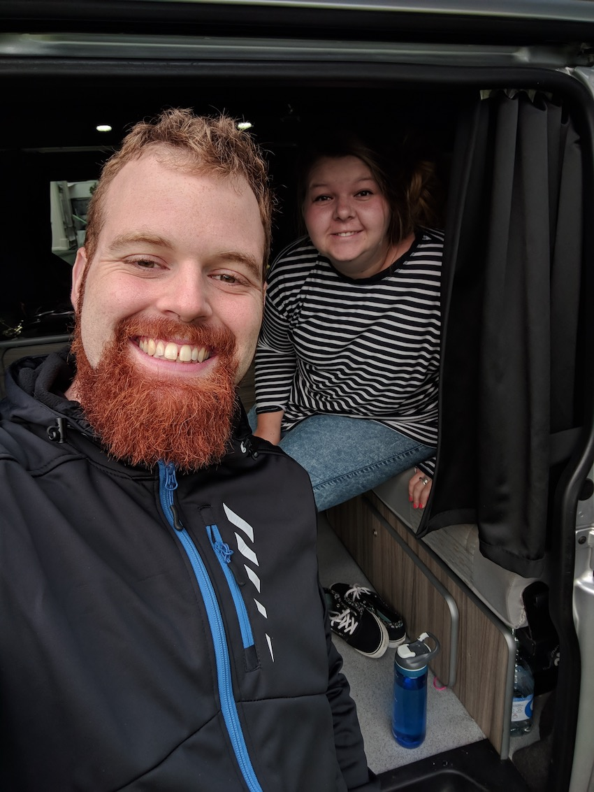 Patchwork couple Lucy and Richard smile at camera from inside a campervan