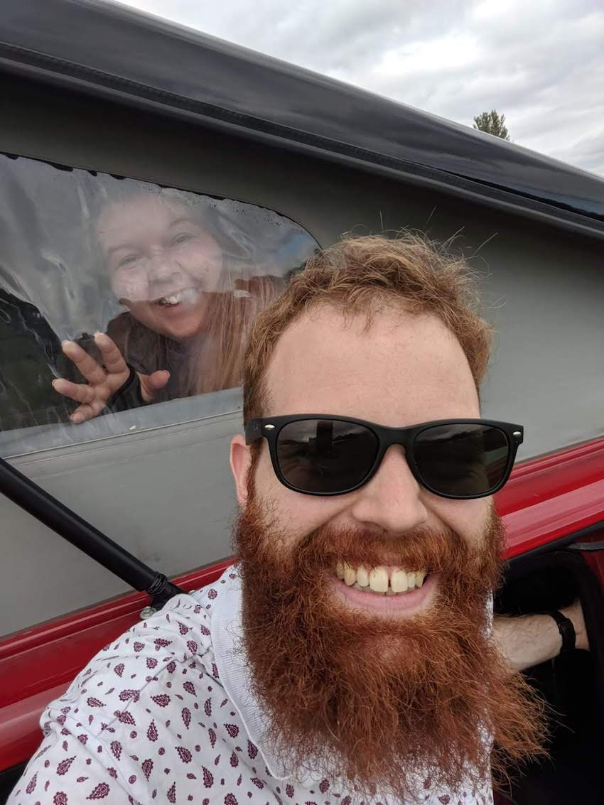 Patchwork couple Lucy and Richard smile at camera, Lucy is inside campervan looking through window and Richard is standing outside wearing sunglasses