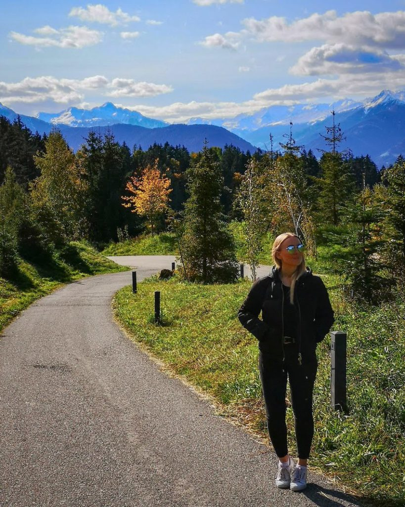 Blond woman stands on narrow country lane in Italy on a bright sunny day with mountains in the distance