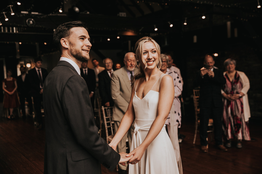 Bride Tash and Groom David stand facing each other and holding hands, both looking to the same side, with their guests in the background