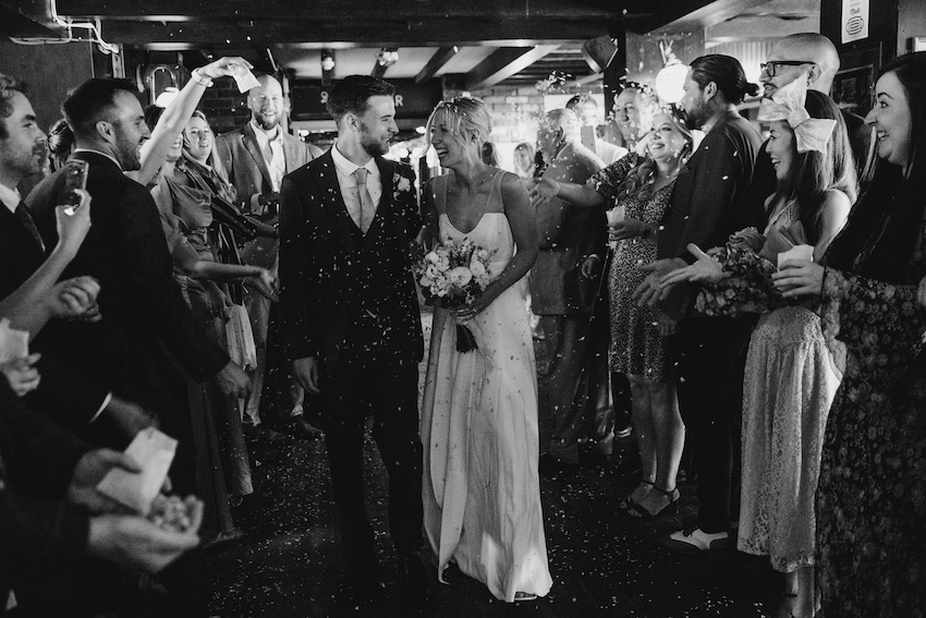 Black and white image of Patchwork couple Tash and David on their wedding day, being showered with confetti by guests