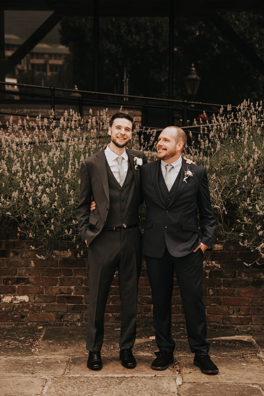 Groom and best man stand together with arms round each others' waists. Both wear dark suits and stand in front of a low wall with flowers above it