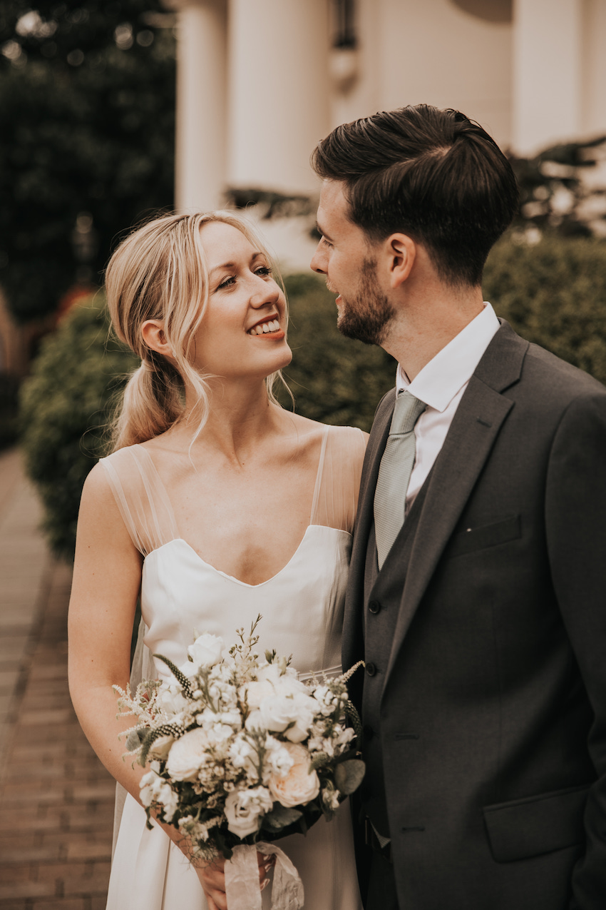 Patchwork couple Tash and David, standing outside on their wedding day, looking in to each others eyes. David wears a dark suit, Tash wears a simple ivory satin dress