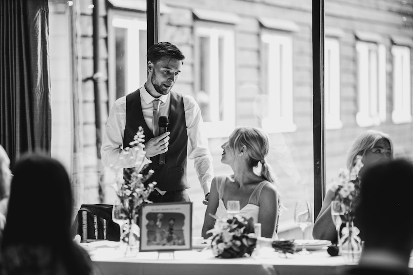 Black and white image of Patchwork couple Tash and David on their wedding day, David is giving his speech and looking down at Tash who is seated