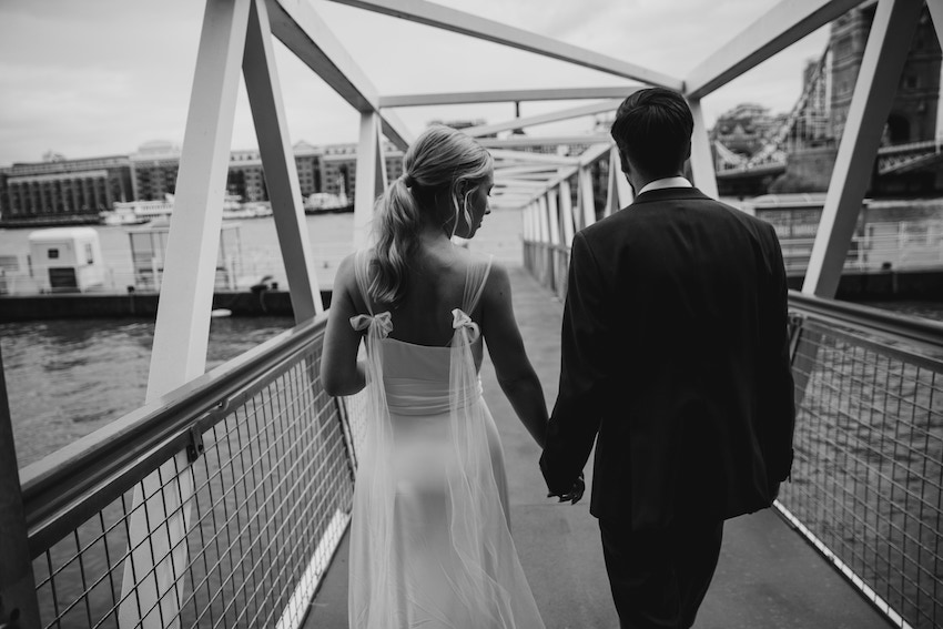 Black and white image of Bride Tash and Groom David walking away from camera, crossing footbridge over River Thames, holding hands.