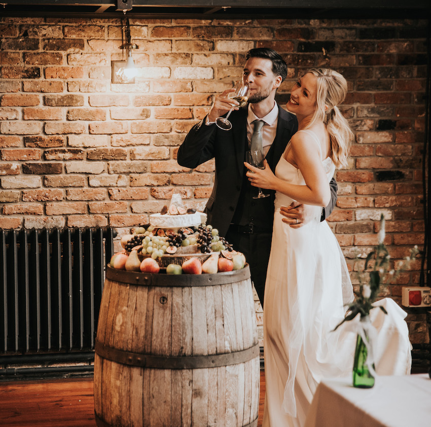 Bride Tash and Groom David, stand together, David's arm round Tash's waist, they both hold a glass of wine each and stand in front of their cheese wedding 'cake'