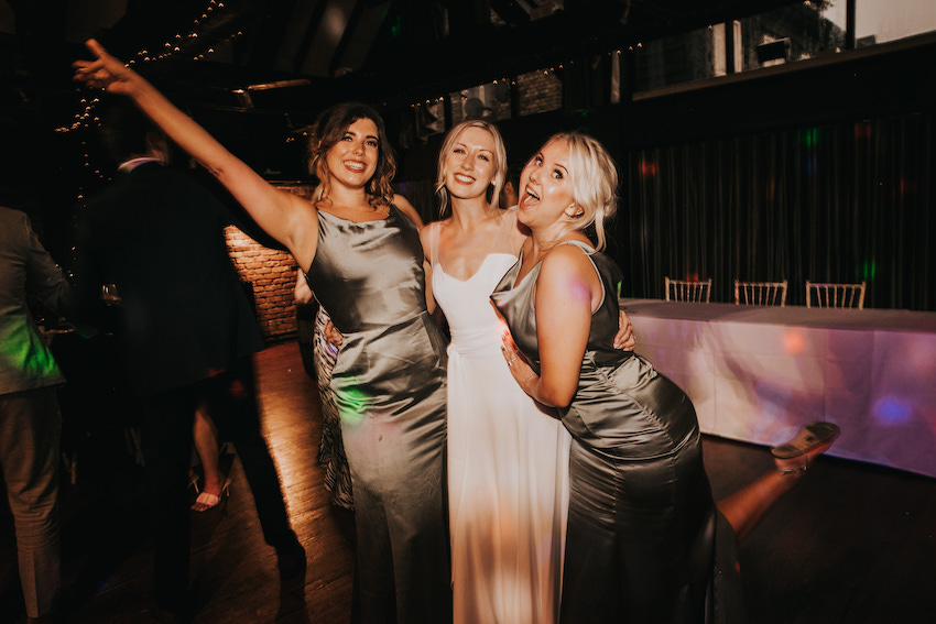 Bride Tash with two female friends either side of her, at her wedding reception, all looking in party spirit