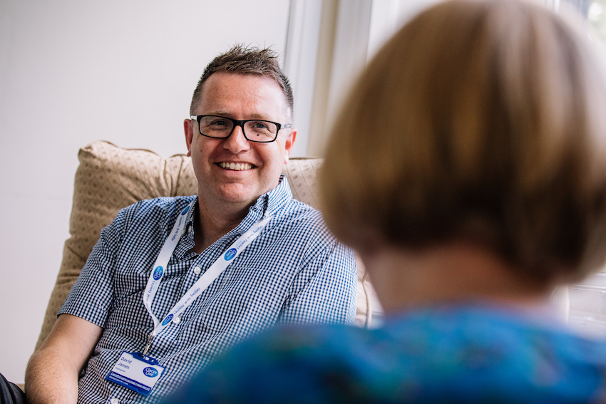 Cancer Care support worker - a white man with glasses and short greyish hair, talking to someone who is front of image but blurred
