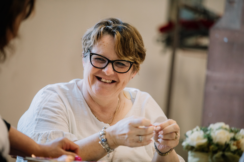 mature white woman wearing glasses and with short dark blonde hair, laughing with someone off camera