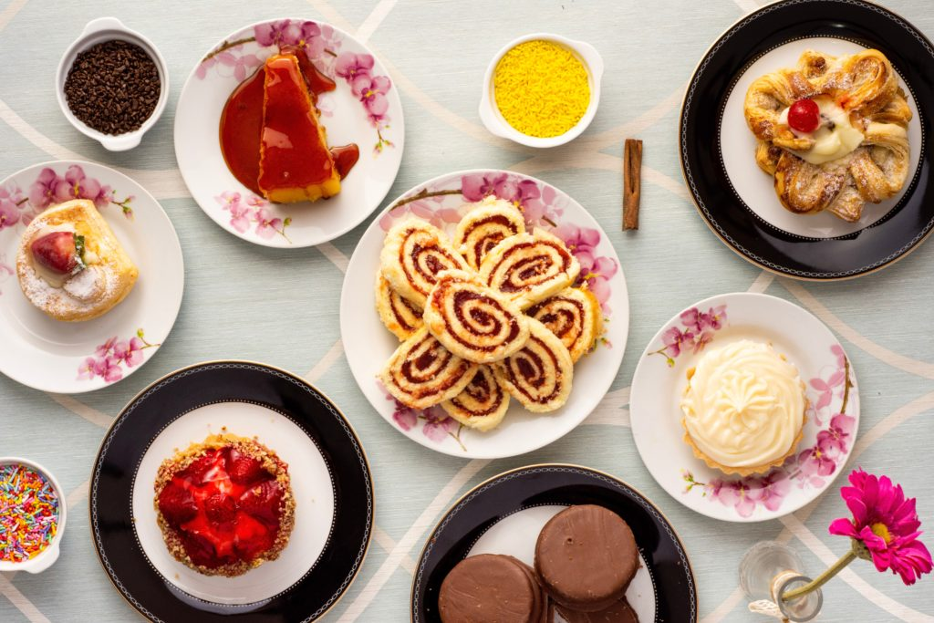 variety of desserts, cakes and sweet treats, flat lay on pale blue table cloth