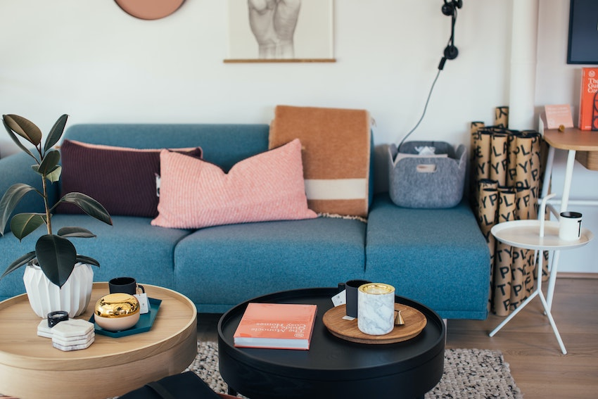 living room with blue sofa, cushions, side tables and decor items