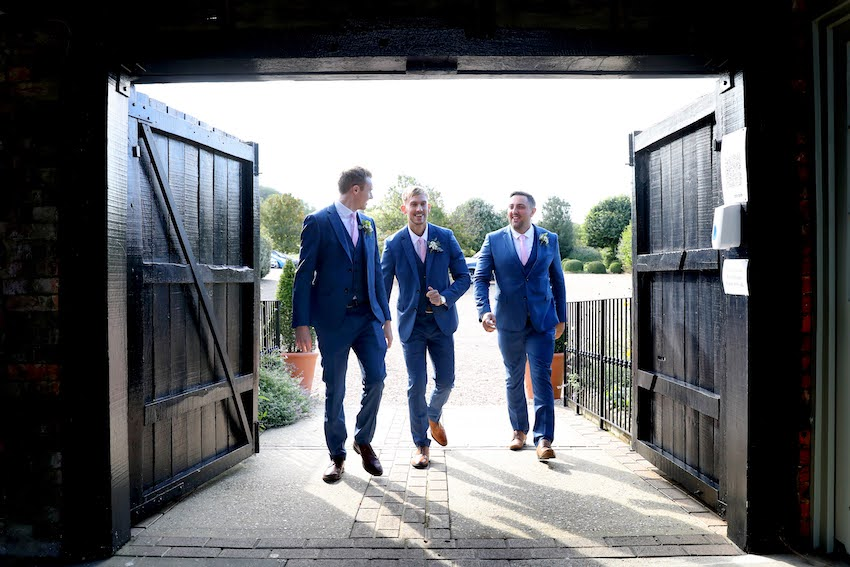 Groom with two groomsmen enter barn through double doors. Men are white and all wear blue suits
