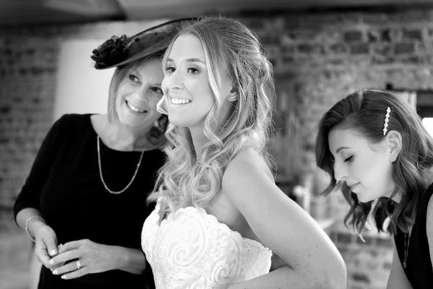 Black and white image of bride (young white woman with long blond hair) stands smiling in her wedding dress with older female next to her and friend attending to her dress