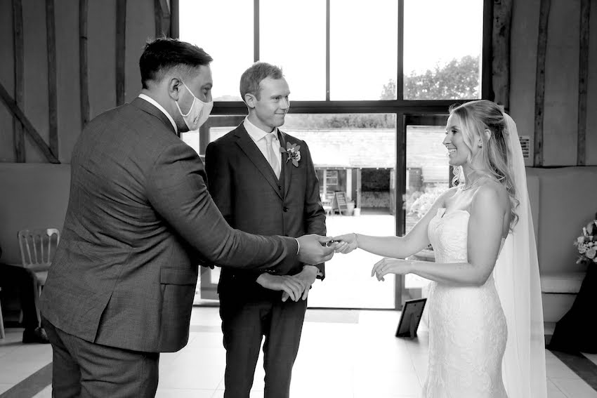 Black and white image of bride (white woman with long blond hair) and groom (tall, slim white man with short fair hair) during wedding ceremony at Upwaltham Barns
