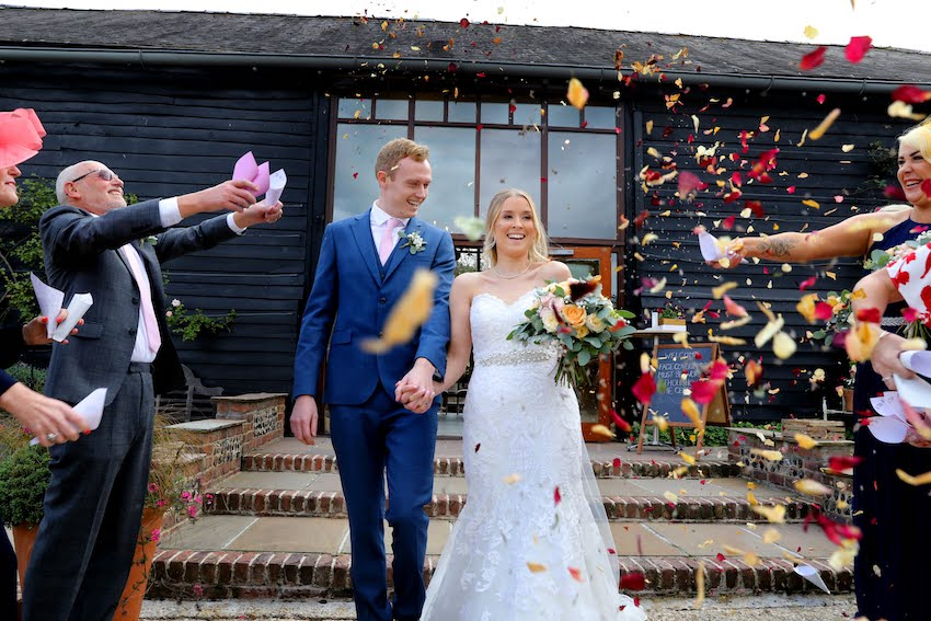 Bride (young white woman with long blond hair) and groom (young white man in blue suit) walk down steps after ceremony as guests throw confetti
