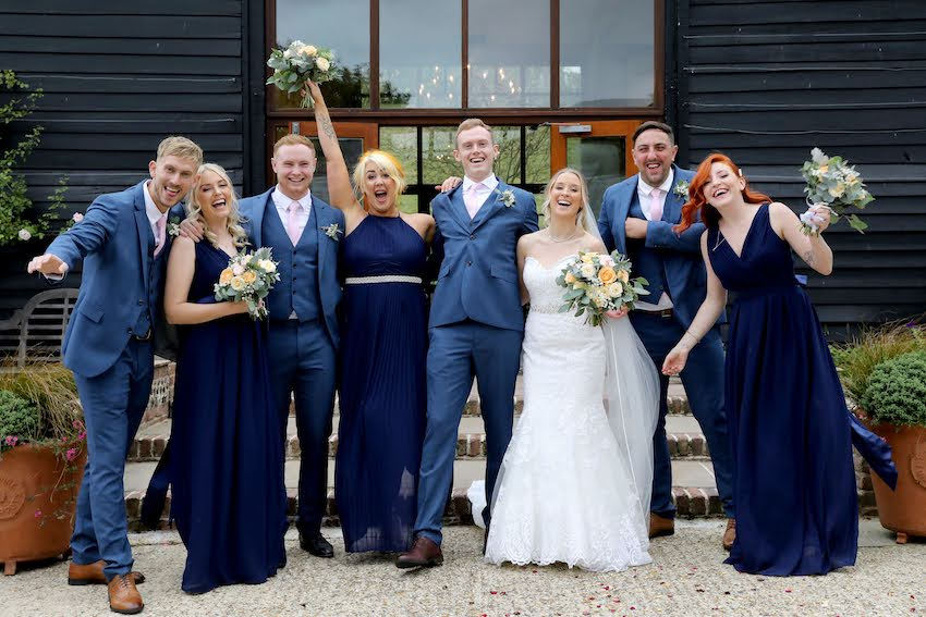 Bride (young white woman with long blond hair) and groom (young white man in blue suit) stand surrounded by bridal party all dressed in blue and smiling at camera