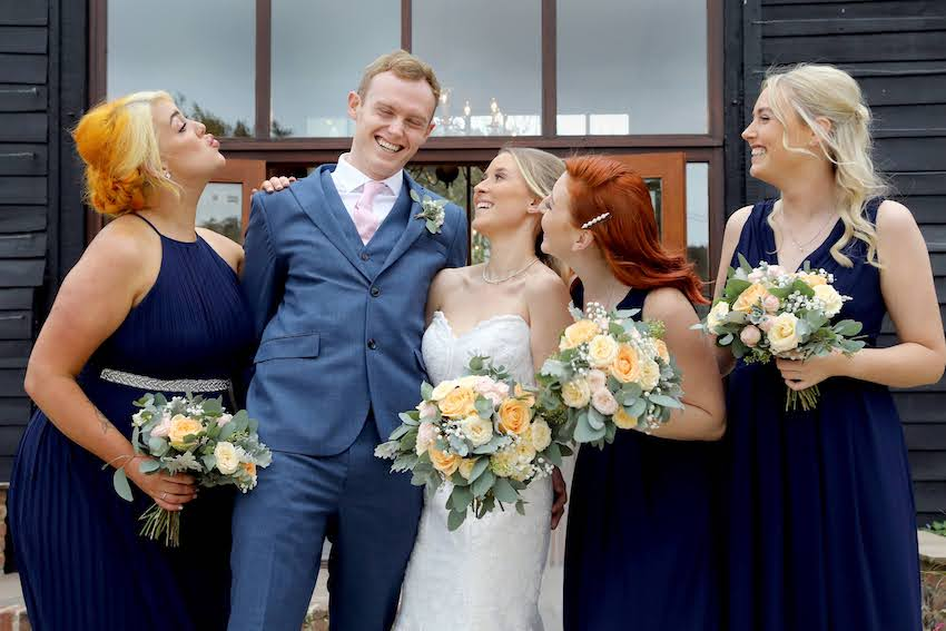 Bride (young white woman with long blond hair) and groom (young white man in blue suit) stand with bridesmaids on either side all the females hold a bouquet of flowers each