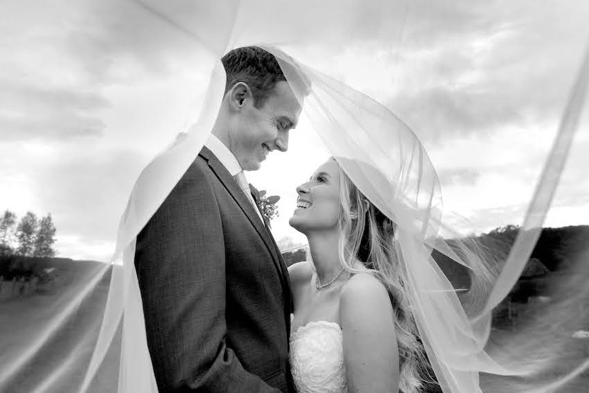 Black and white image of Patchwork couple Liz and Jack standing close together with Liz's veil swirled above them, they look at each other, smiling
